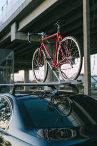 Nosilec za kolo drži na avtu rdeče cestno kolo.